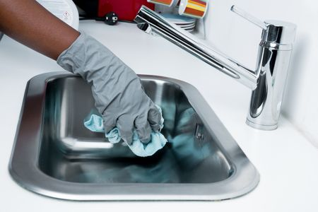 Hand with rubber glove cleaning kitchen sink.