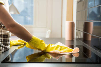 Woman's hand wearing yellow glove and cleaning the surface of the stove in a home in Pompano Beach, FL.